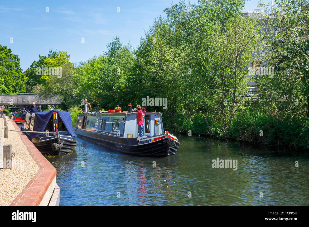 Narrowboat sailing on the Basingstoke Canal passing through Woking town centre by the Saturn Trail, Surrey, southeast England on a sunny day Stock Photo