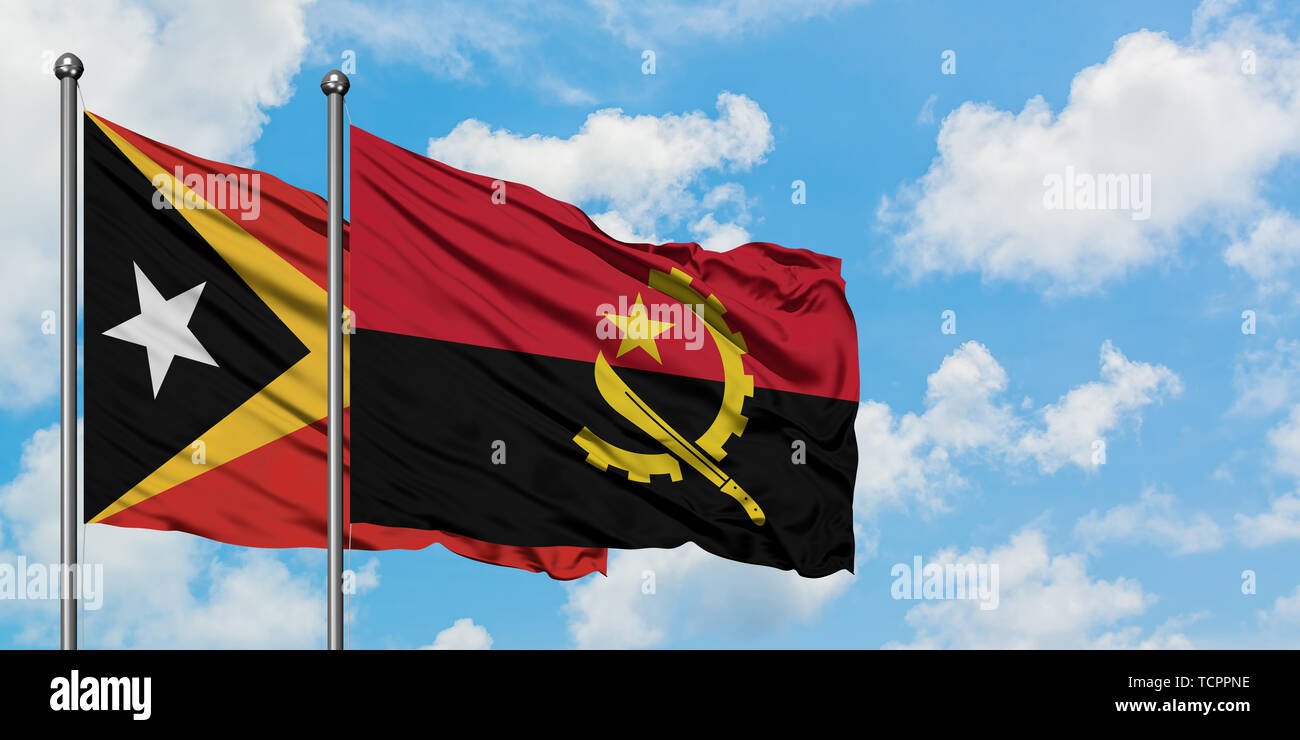 East Timor and Angola flag waving in the wind against white cloudy blue sky together. Diplomacy concept, international relations. - Stock Image