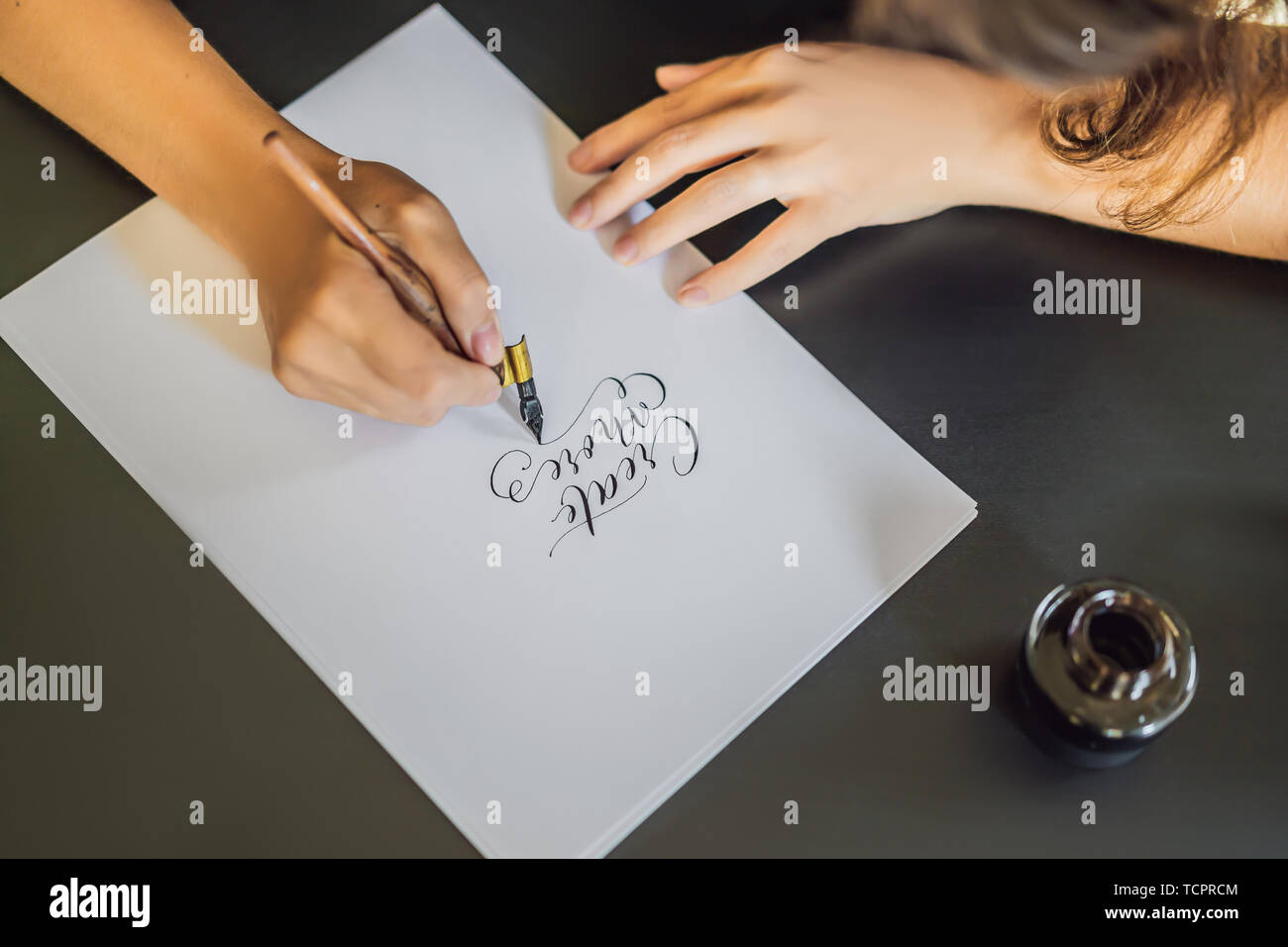 Creat more. Calligrapher Young Woman writes phrase on white paper. Inscribing ornamental decorated letters. Calligraphy, graphic design, lettering - Stock Image