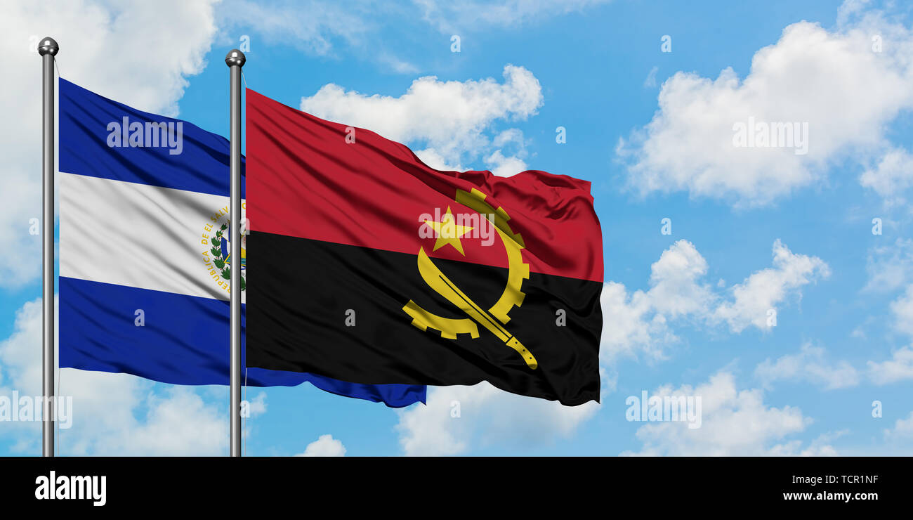 El Salvador and Angola flag waving in the wind against white cloudy blue sky together. Diplomacy concept, international relations. - Stock Image