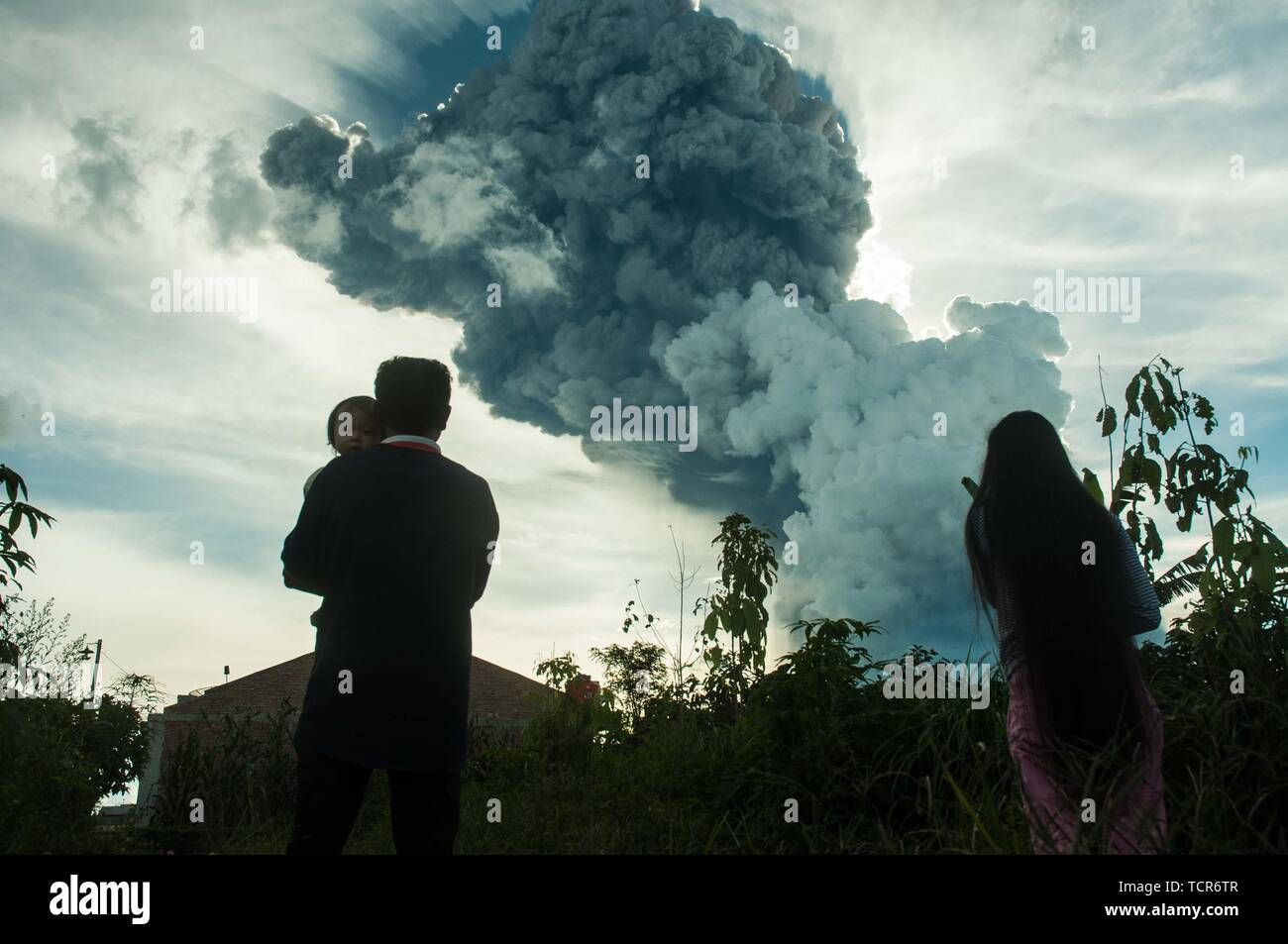"Sumatra, Indonesia. 09th June, 2019. The eruption of Mt. Sinabung, North Sumatra on June 9, 2019 at 16:28 with the ash column height observed ± 7,000 m above the peak (± 9,460 m above sea level). The ash column was observed to be black with thick intensity leaning southward. Seen from kabanjahe city. ""There was a hot cloud in the 3.5 km southeast and 3 km south and a roar came to the volcano observation post of Sinabung Currently Mount Sinabung is in Status * Level III (Standby)' Said vulcano officer guard from radio communication. Credit: Sabirin Manurung/Pacific Press/Alamy Live News Credit: Stock Photo"