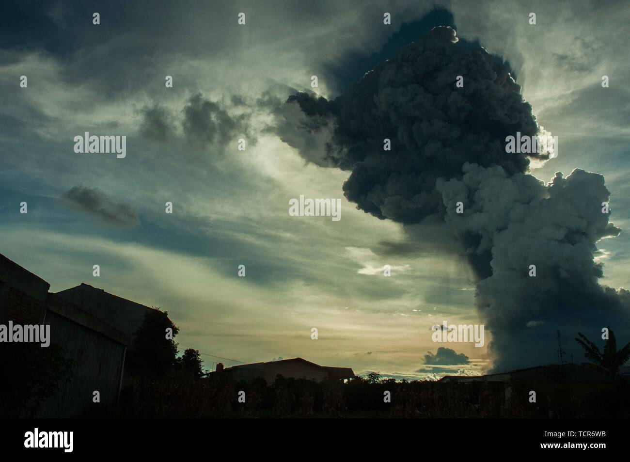 """Sumatra, Indonesia. 09th June, 2019. The eruption of Mt. Sinabung, North Sumatra on June 9, 2019 at 16:28 with the ash column height observed ± 7,000 m above the peak (± 9,460 m above sea level). The ash column was observed to be black with thick intensity leaning southward. Seen from kabanjahe city. """"There was a hot cloud in the 3.5 km southeast and 3 km south and a roar came to the volcano observation post of Sinabung Currently Mount Sinabung is in Status * Level III (Standby)' Said vulcano officer guard from radio communication. Credit: Sabirin Manurung/Pacific Press/Alamy Live News Credit: Stock Photo"""
