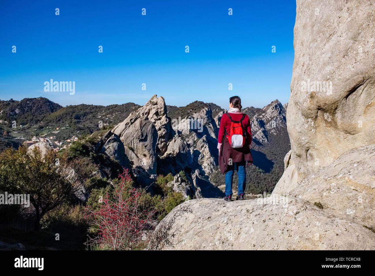 Woman admires the landscape of Dolomites of Basilicata mountains called Dolomiti Lucane. Basilicata region, Italy - Stock Image