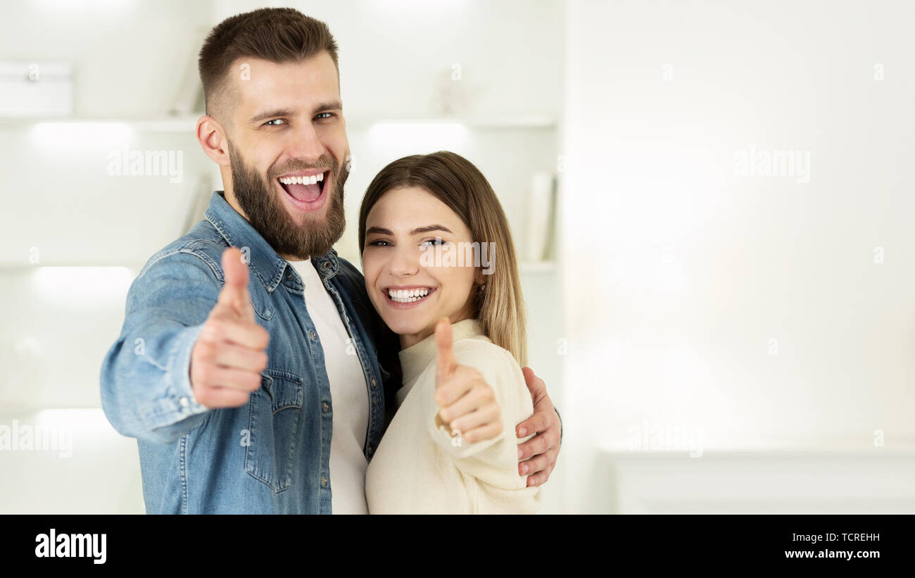Couple Recommending Real Estate Agency, Showing Thumbs Up - Stock Image