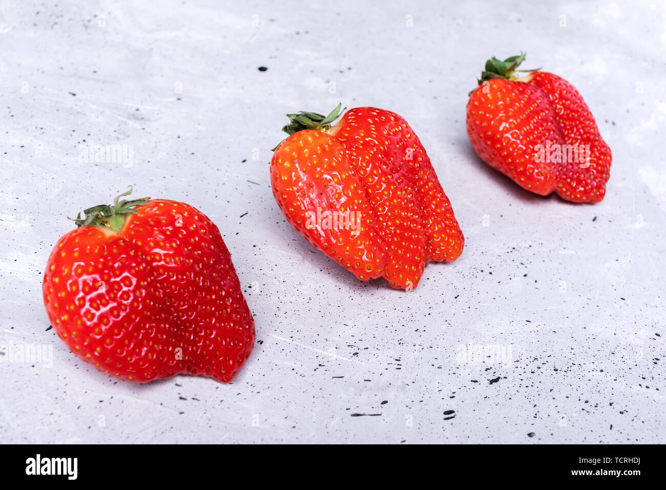 Three ugly strawberries are lying diagonally on grey concrete background.  - Stock Image
