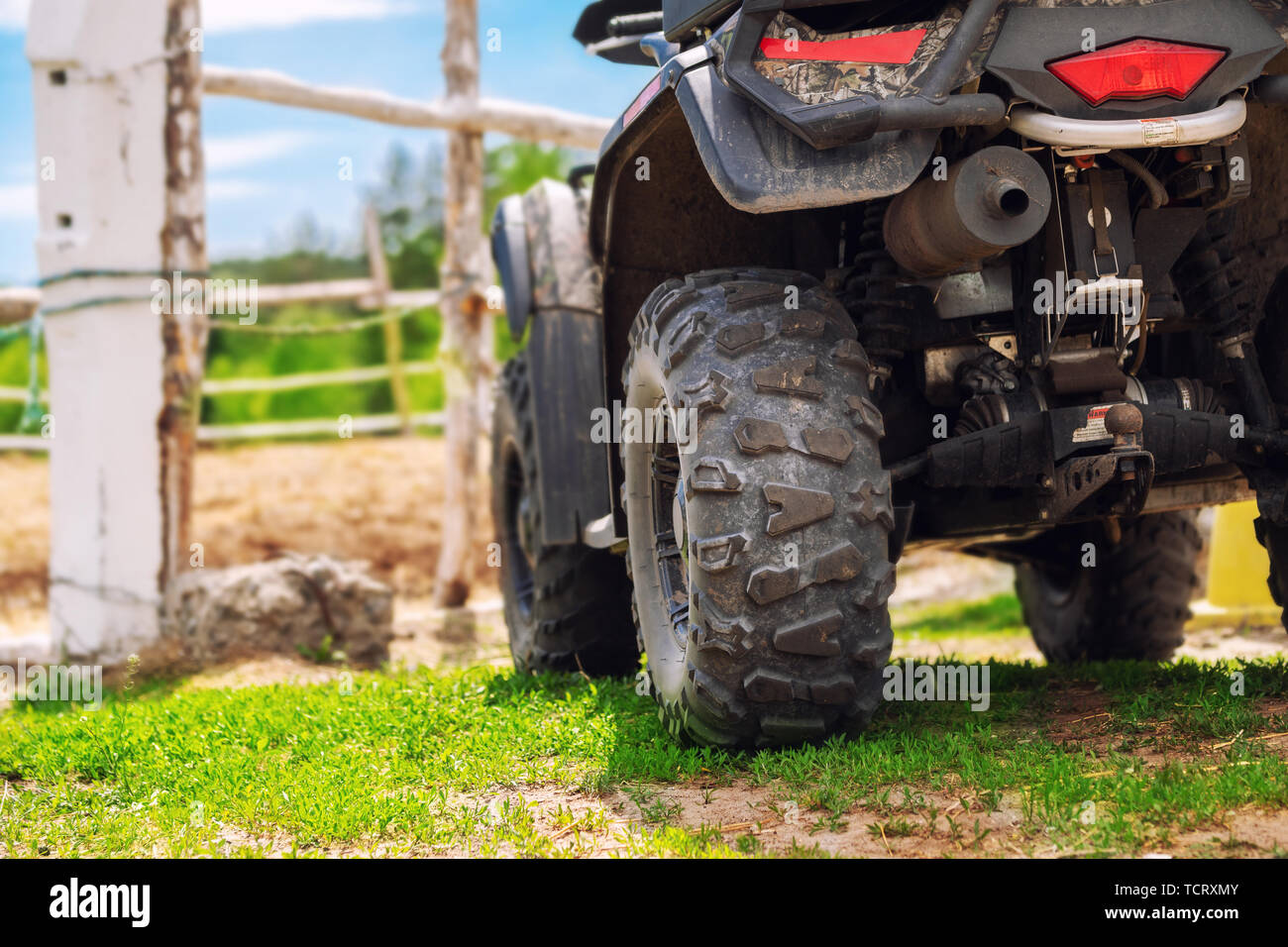 ATV quad bike vehicle standing near wooden fence at farm or horse stable. Back view of all wheel drive motorcycle at farm. Rural countryside machine Stock Photo