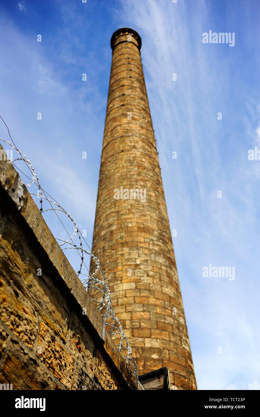 Razor wire on top of stone wall with old factory mill chimney against sky in the background - Stock Image