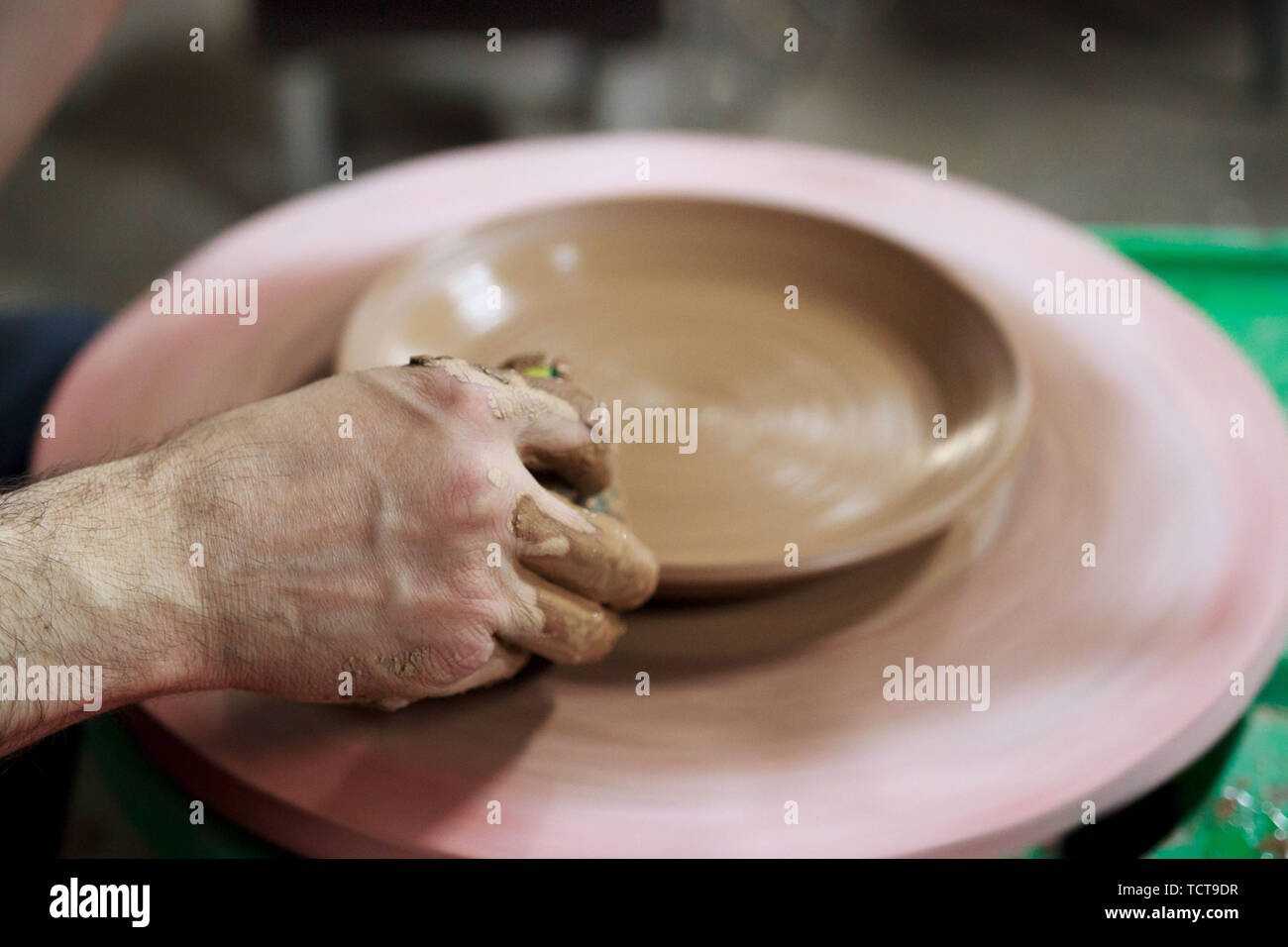 a master ceramist with 13 years of experience makes plate from red clay on a potter's wheel, on a sheet of particle board for better removal and furth Stock Photo