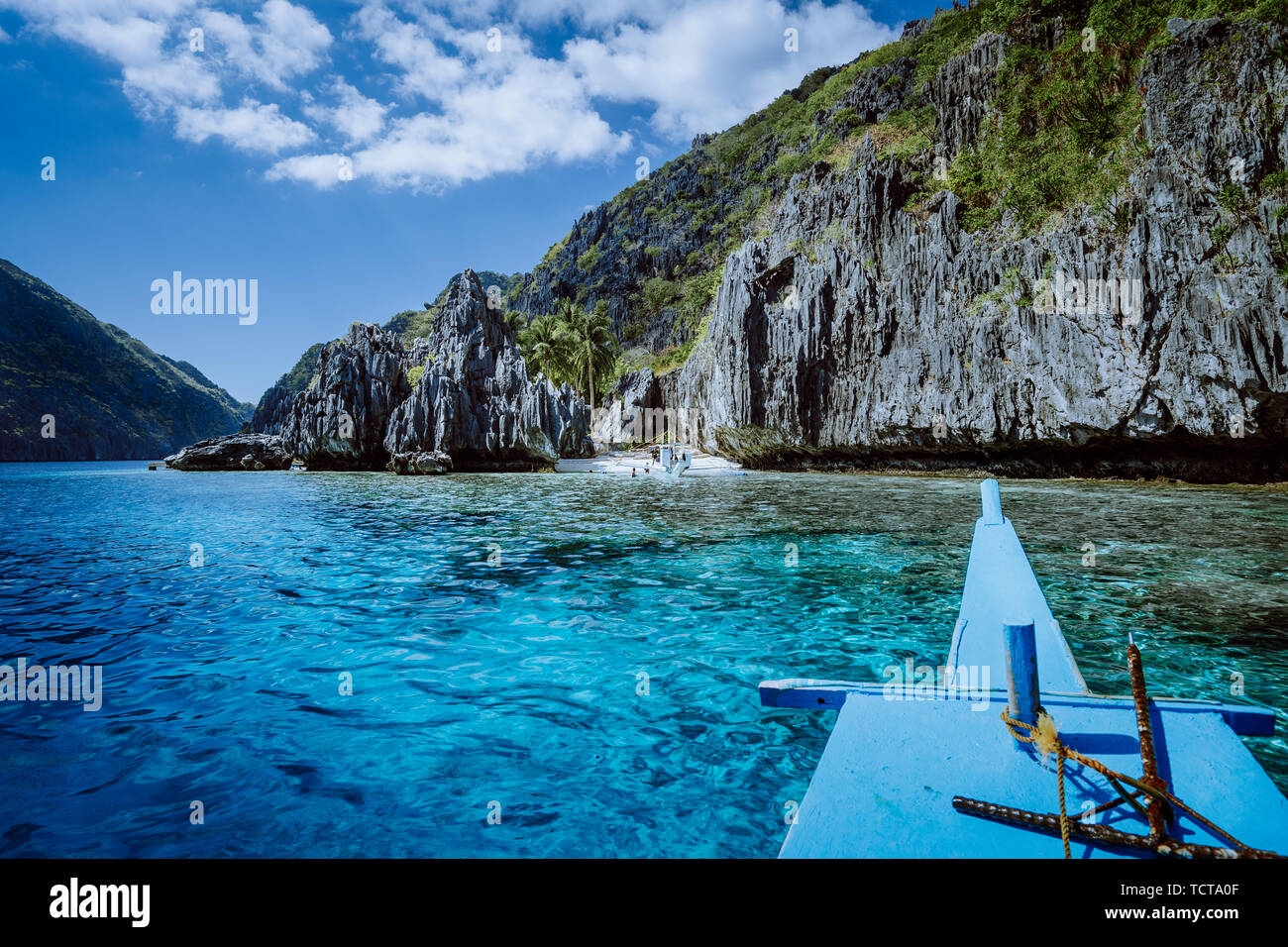 Banca boat approaching small beach at the Shrine, on Matinloc island, highlights of hopping trip Tour C. Must see, most beautiful place at Marine - Stock Image