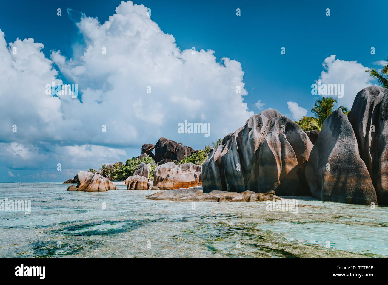 Famous granite boulders in lagoon with shallow ocean water and white cloudscape on amazing Anse Source D'Argent tropical beach, La Digue Seychelles Stock Photo