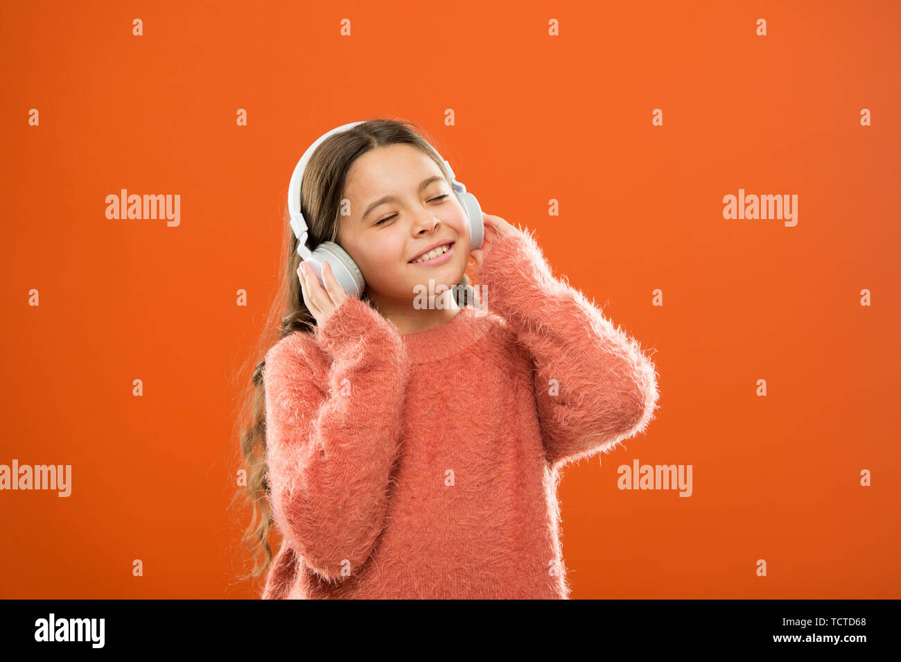 Girl cute little child wear headphones listen music kid listen music orange background recommended music based on initial interest best free music apps