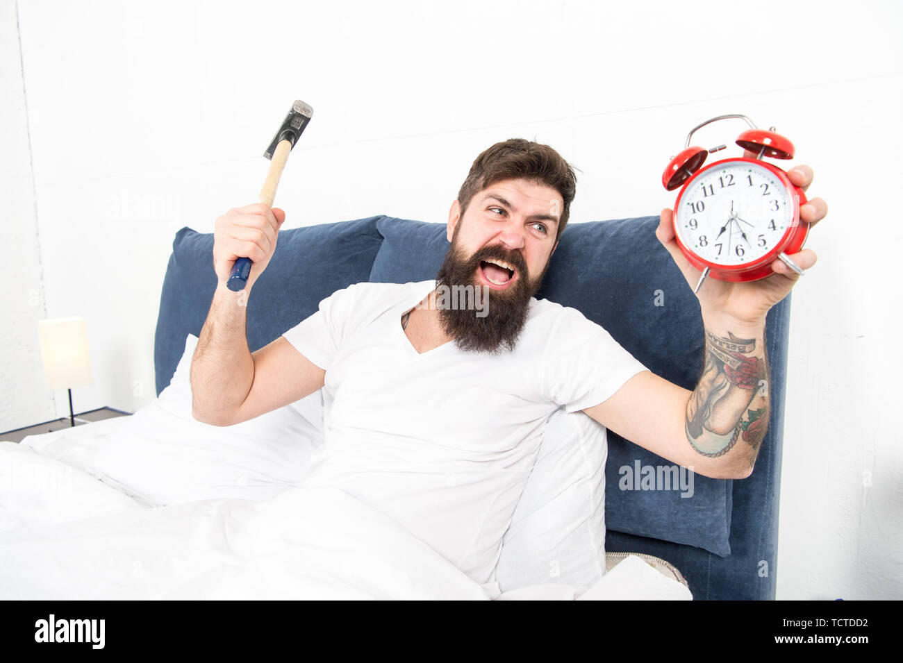 It is totally normal to hate your alarm sound. Hateful schedule. Best alarm clocks for people who hate mornings. Man bearded hipster hate wake up early. Destructive energy. Hardest moment of day. - Stock Image