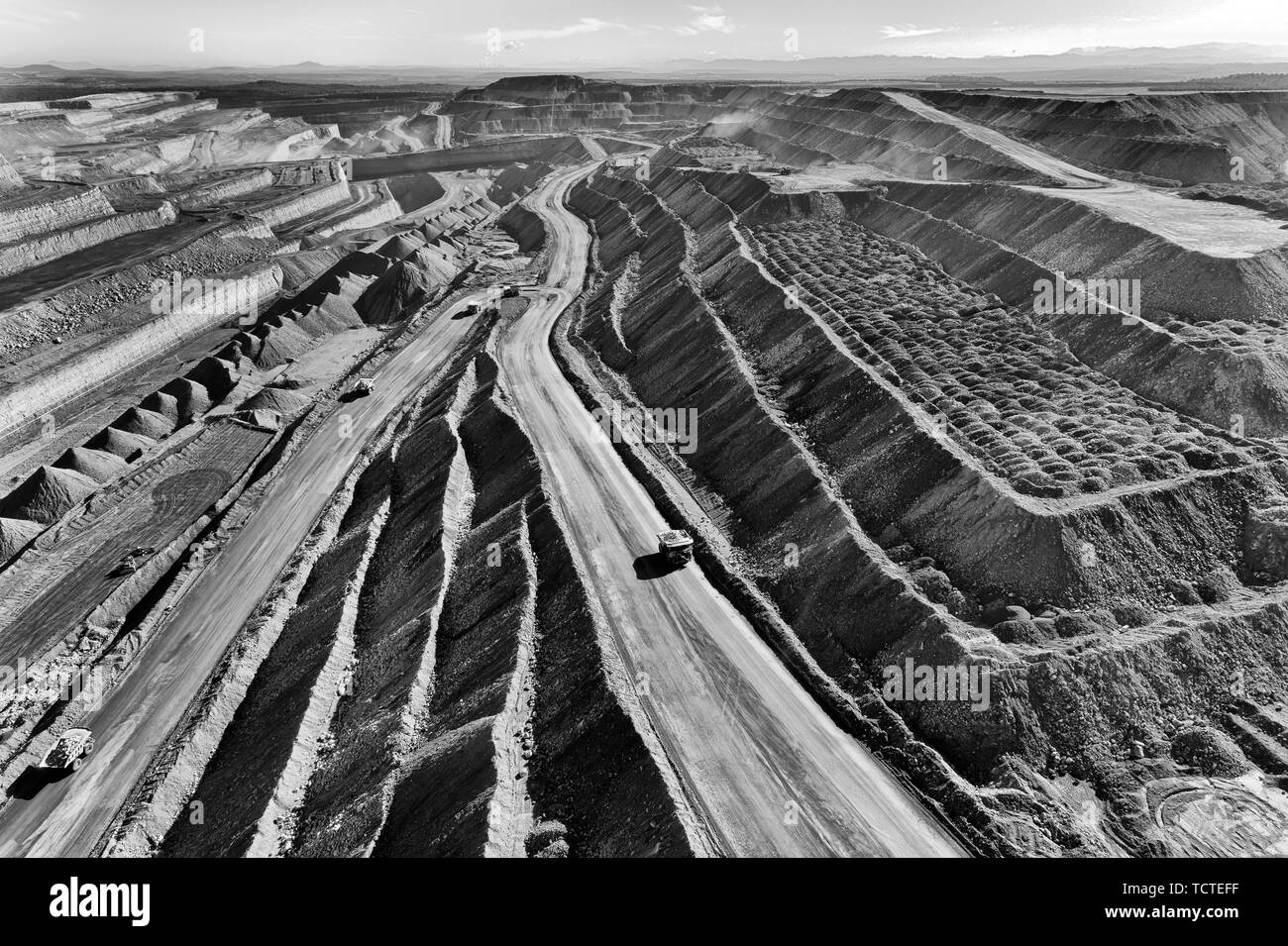 Open cut coal mine in Hunter valley region supplying Liddell and Baywaters power stations excavating coal by huge trucks from the botton via serpentin Stock Photo
