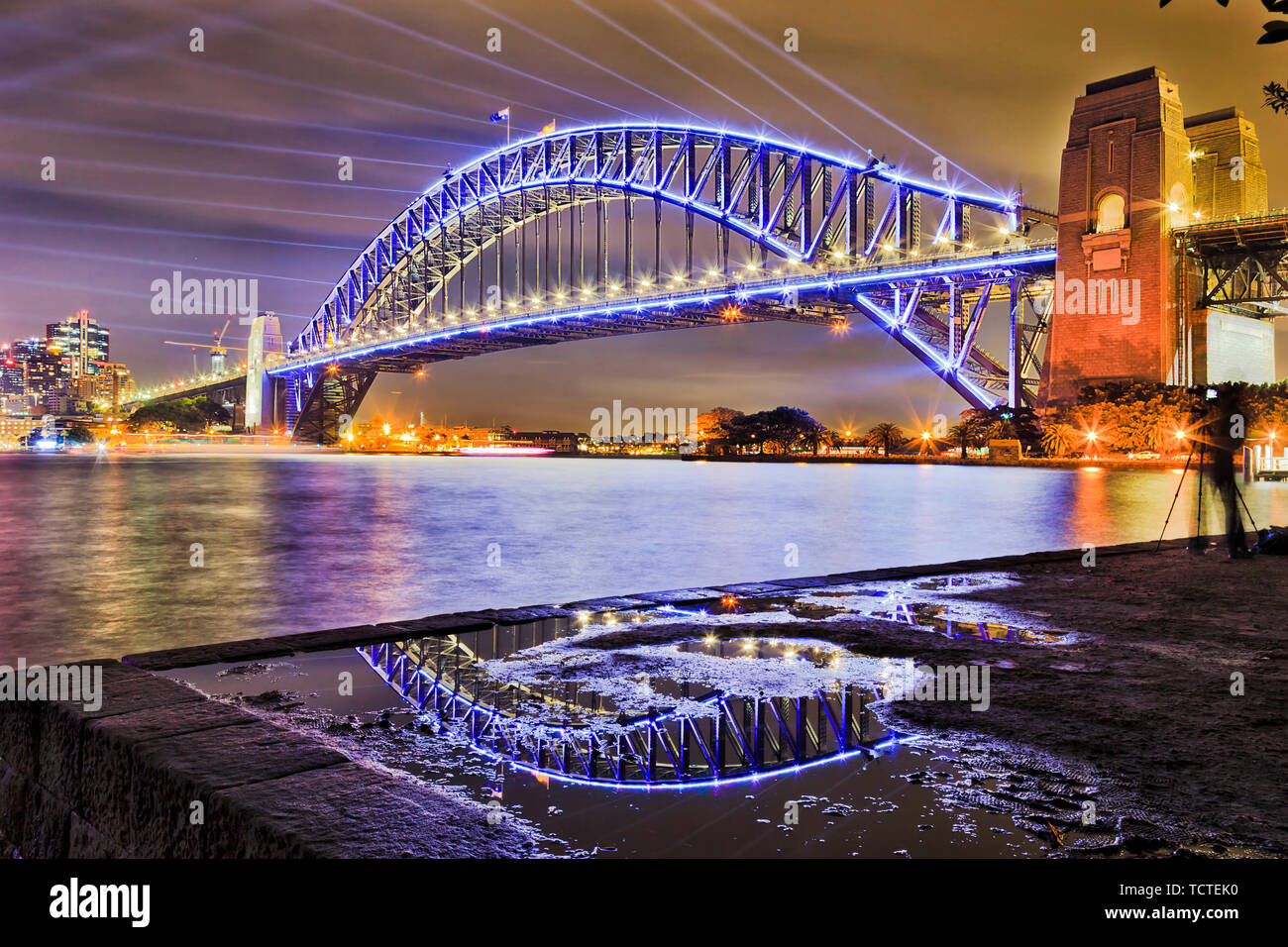 Massive steel arch of the Sydney harbour bridge over Sydney harbour reflecting in puddle with blue laser beams in dark sky at Vivid Sydney light show. - Stock Image