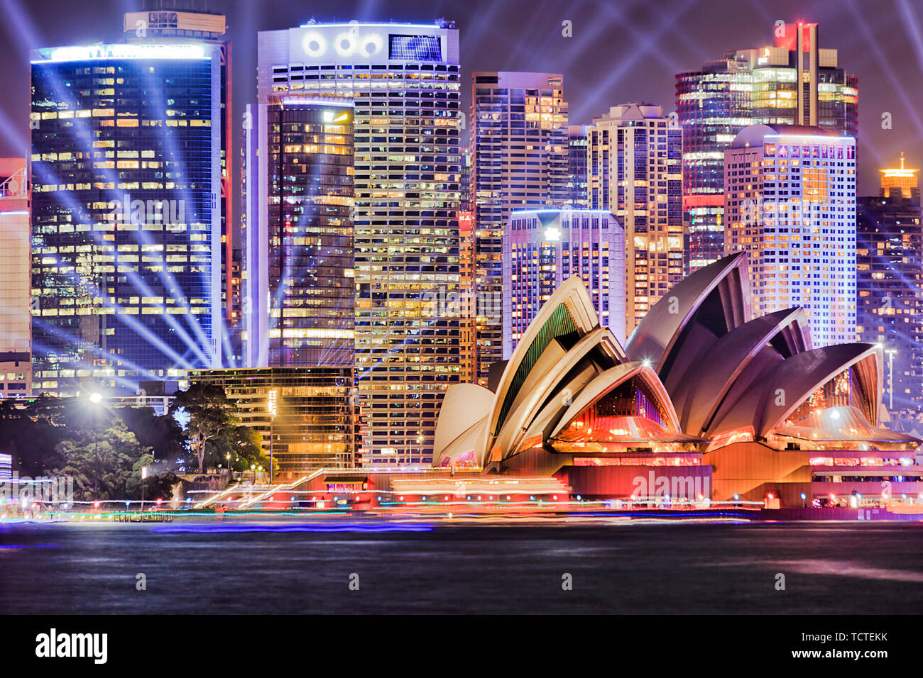 Facades of High-rise office towers of Sydney city CBD on waterfront of Sydney harbour illuminated by blue laser beams of Vivid Sydney light show. - Stock Image