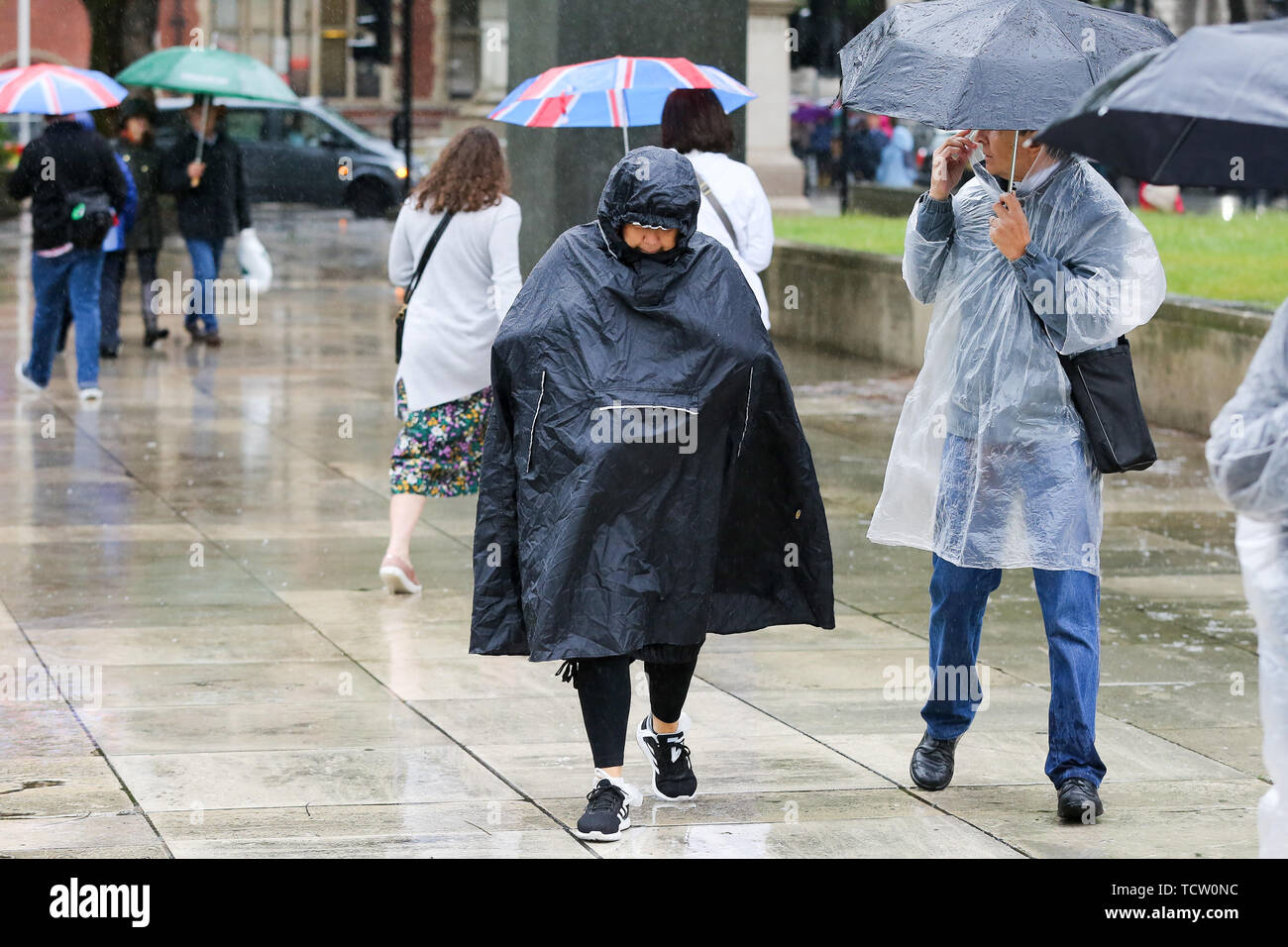 Westminster, London, UK 10 June 2019 - Tourists wearing rain ponchos in Westminster as rain falls in the capital. The Met Office has issued an amber warning for more rain, covering London and parts of southeast England this week.  Credit: Dinendra Haria/Alamy Live News - Stock Image