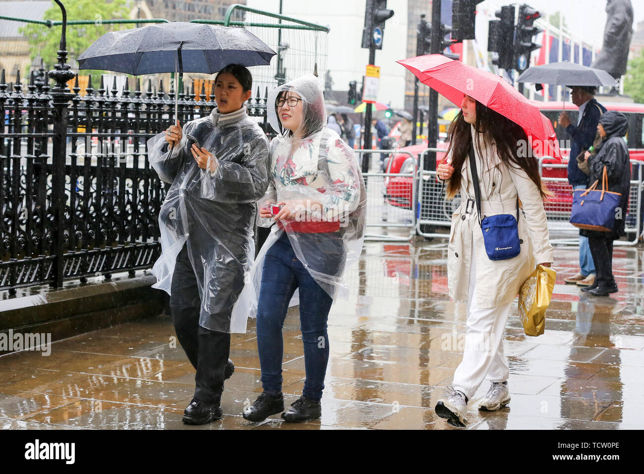 June 10, 2019 - London, UK, United Kingdom - Tourists shelter from the rain beneath umbrellas and wearing rain ponchos as rainfalls in the capital. .The Met Office has issued an amber warning for more rain, covering London and parts of southeast England for this week. (Credit Image: © Dinendra Haria/SOPA Images via ZUMA Wire) - Stock Image