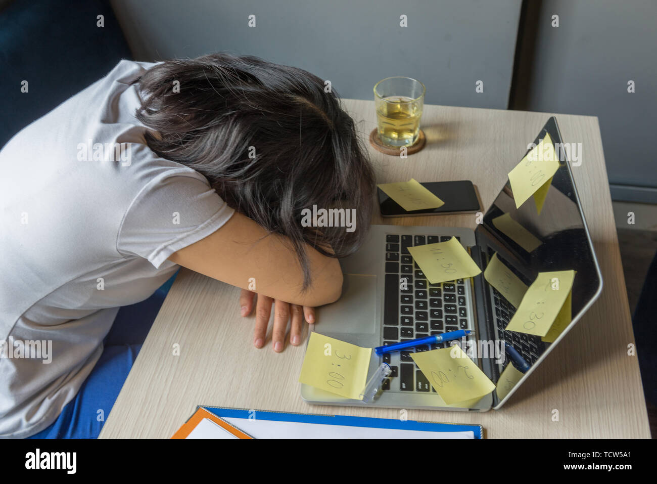 Stressful freelancer female fall asleep on laptop with sticky notes - Stock Image
