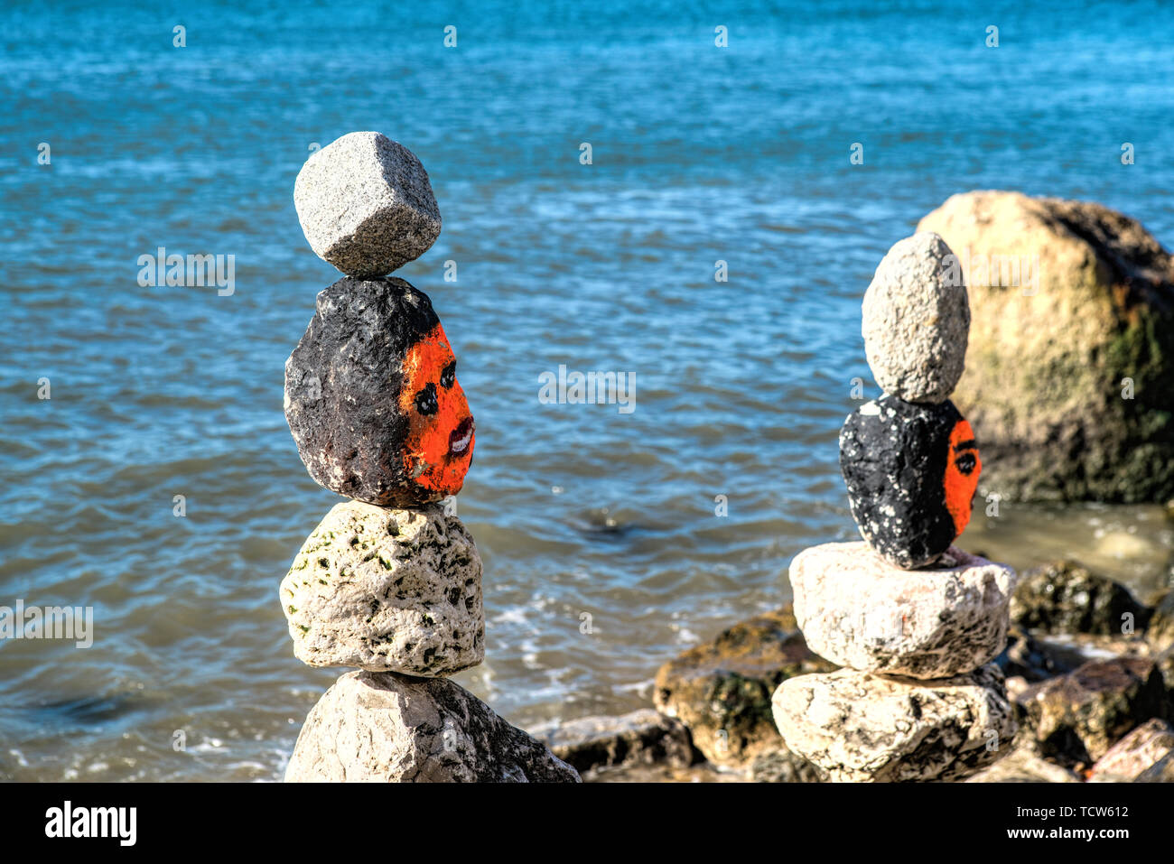 Stone cairn tower, rock zen sculpture near river side in Lisbon - Stock Image