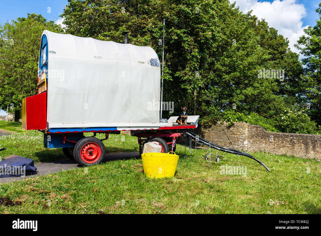 A small plain gypsy vardo caravan unhitched on a grass verge with a small dog sat up front - Stock Image