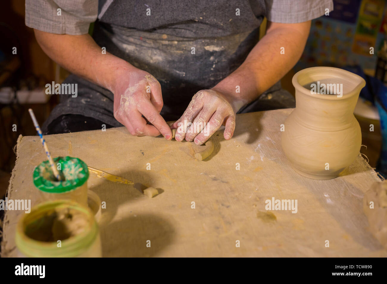 Professional male potter working in workshop, studio - Stock Image