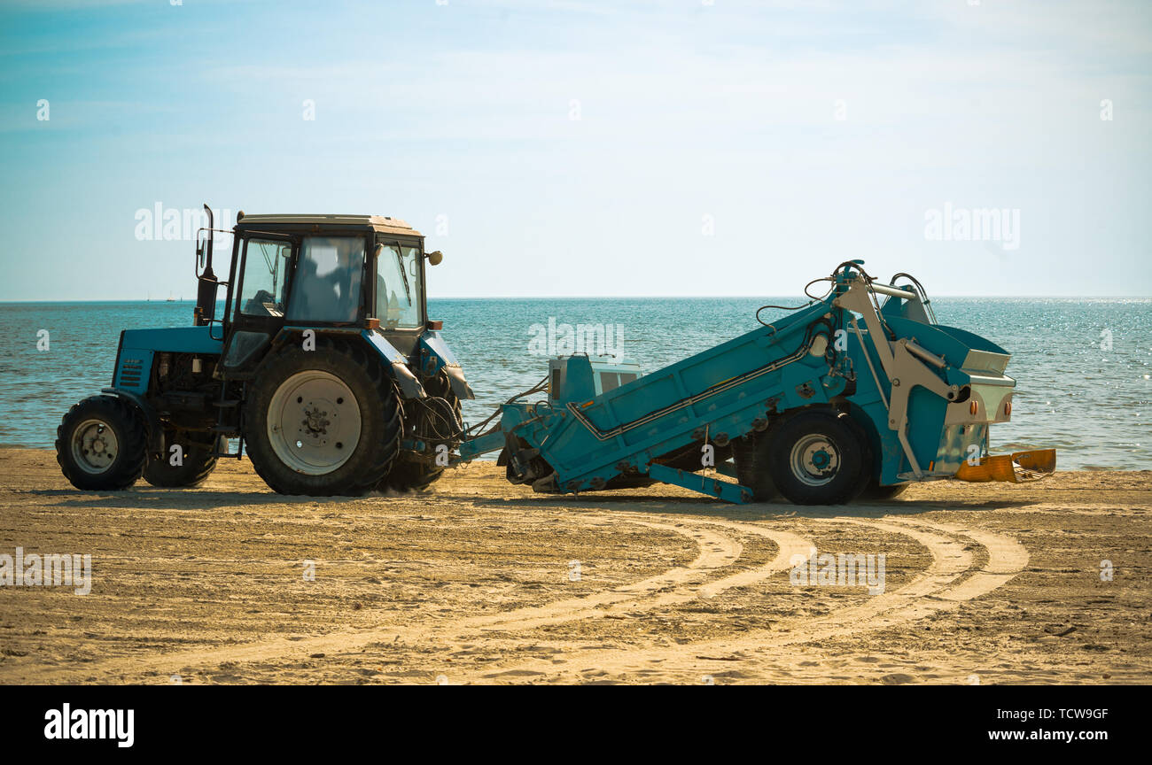 tractor and the beach cleaning machine - Stock Image