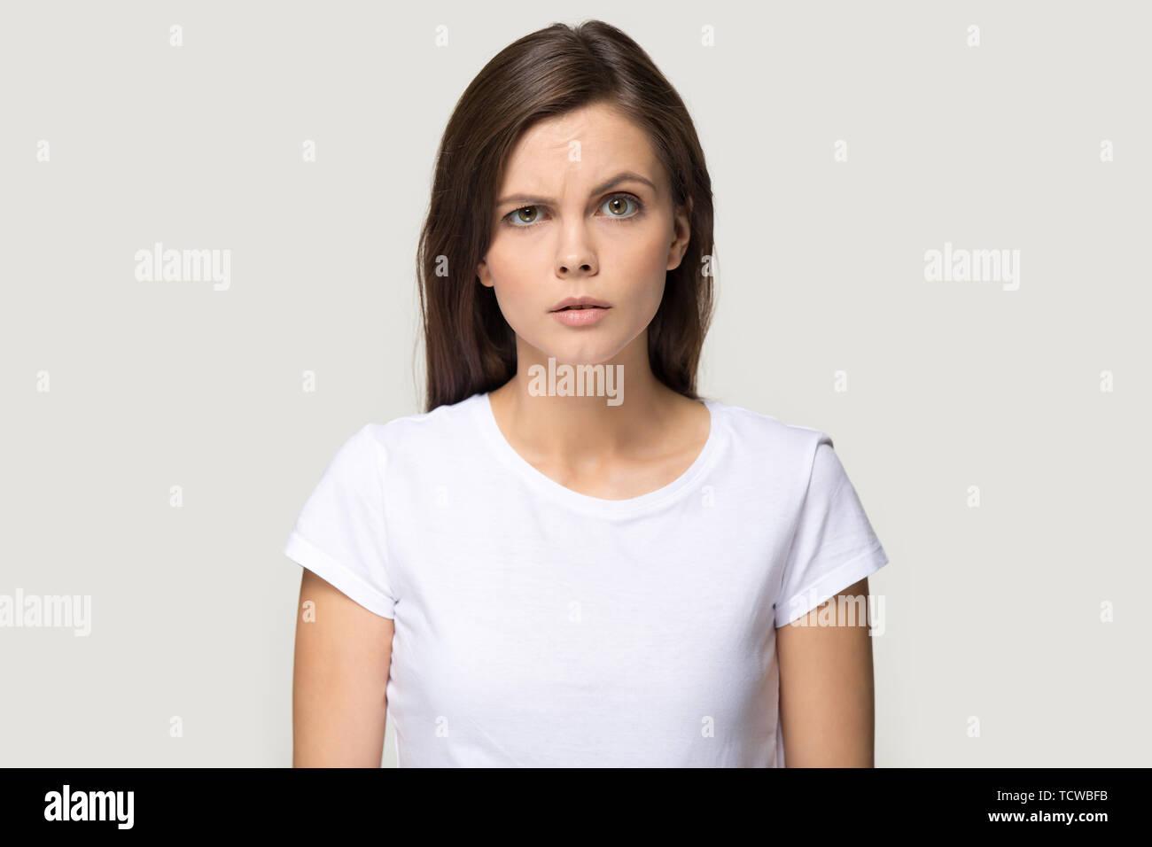 Sceptic suspicious millennial woman pose on grey studio background - Stock Image