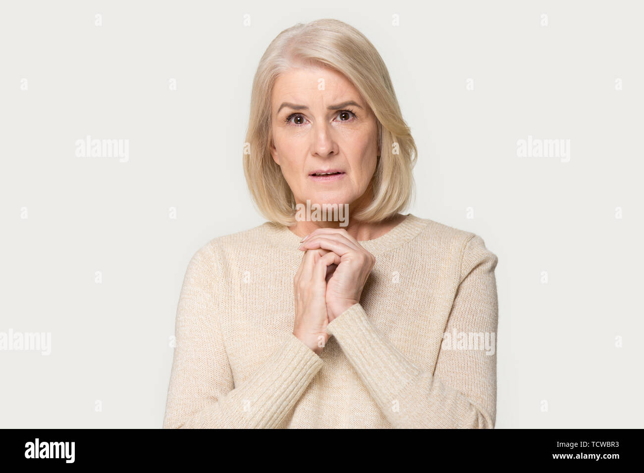 Anxious senior woman folded hands together isolated on grey background - Stock Image