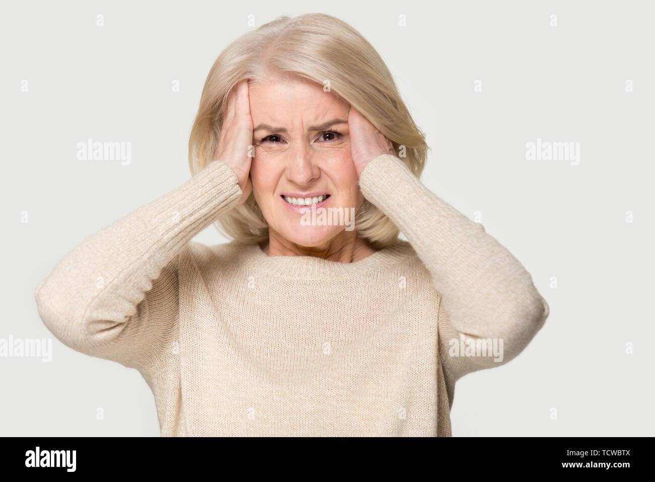 Mature woman holding head in hands feels unhealthy studio shot - Stock Image