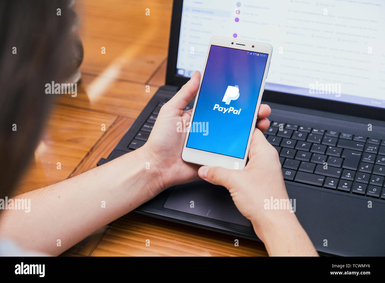 ROSARIO, ARGENTINA - FEBRUARY 16, 2019: Paypal app on the screen of smartphone.Girl in front of a laptop with cell phone in her hands. Logotype. - Stock Image