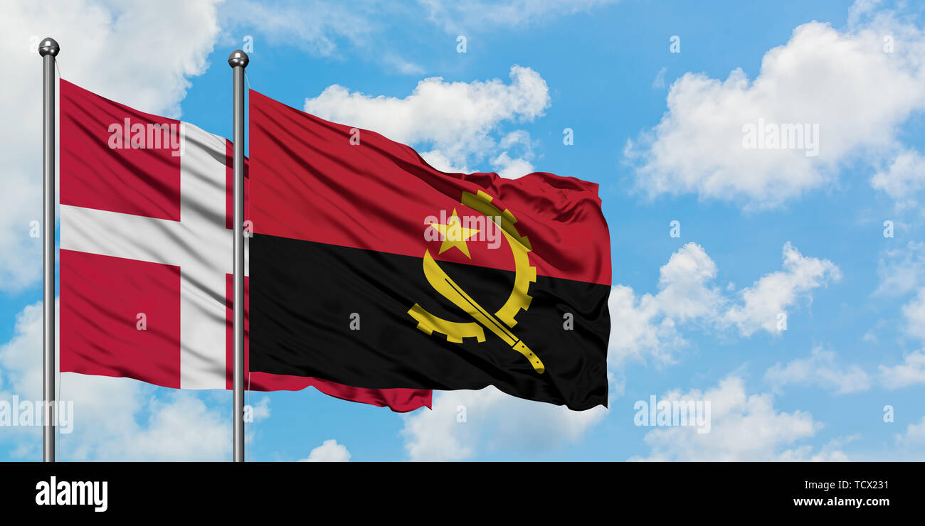 Denmark and Angola flag waving in the wind against white cloudy blue sky together. Diplomacy concept, international relations. Stock Photo