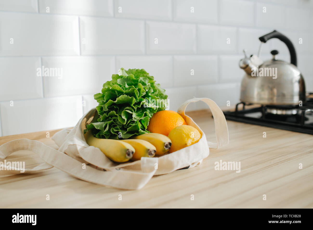 Lettuce, lemon, banana and orange in a white cotton bag in the sunny kitchen, lying on the table. - Stock Image