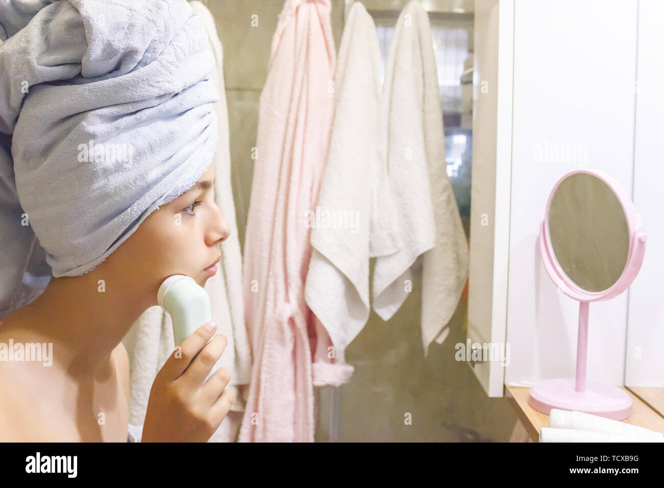 Young beautiful teen girl in towel making facial massage by herself - Stock Image