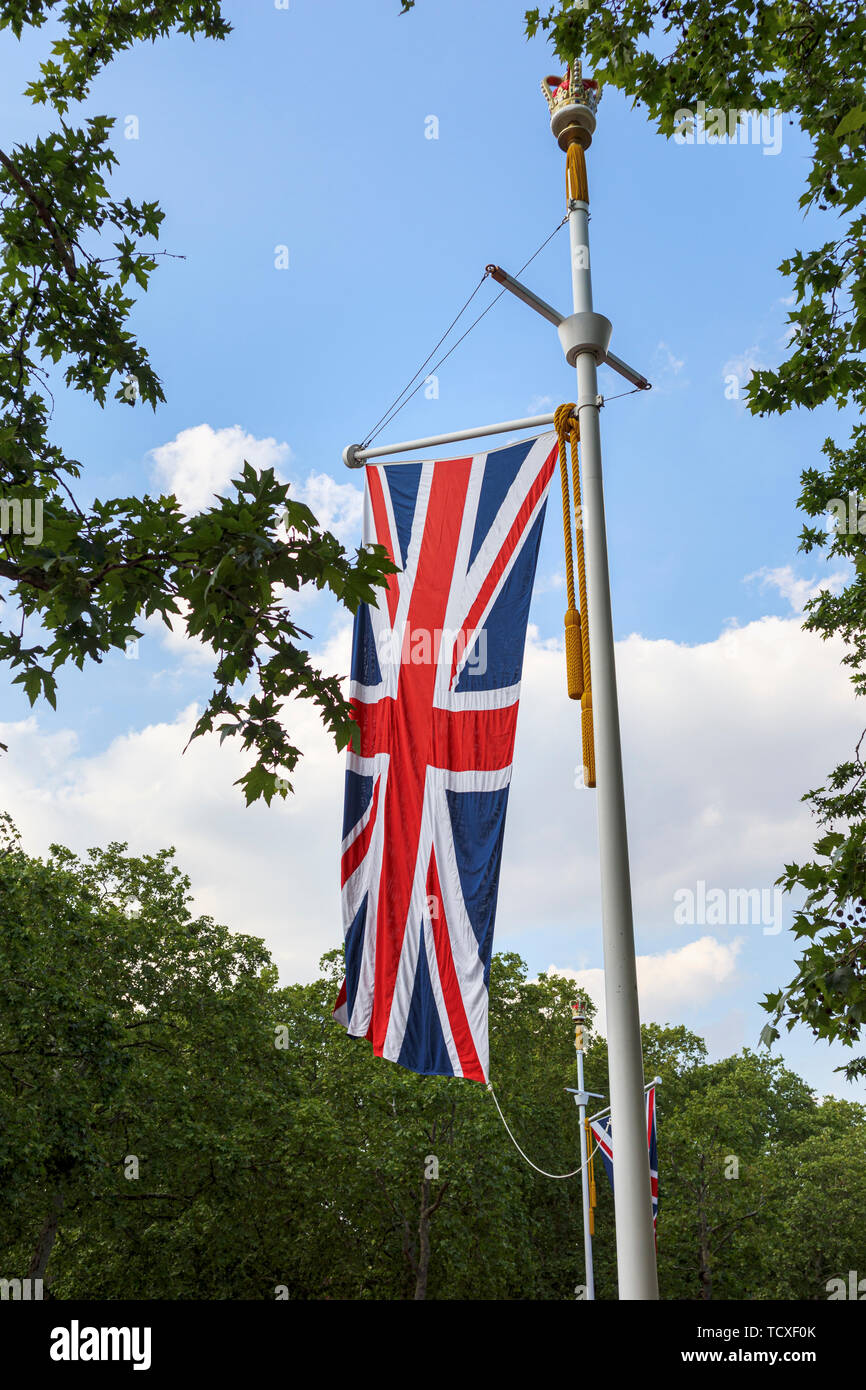 Union Jack flag flying from a roadside flagpole in The Mall, London, UK in spring with green trees and blue sky Stock Photo