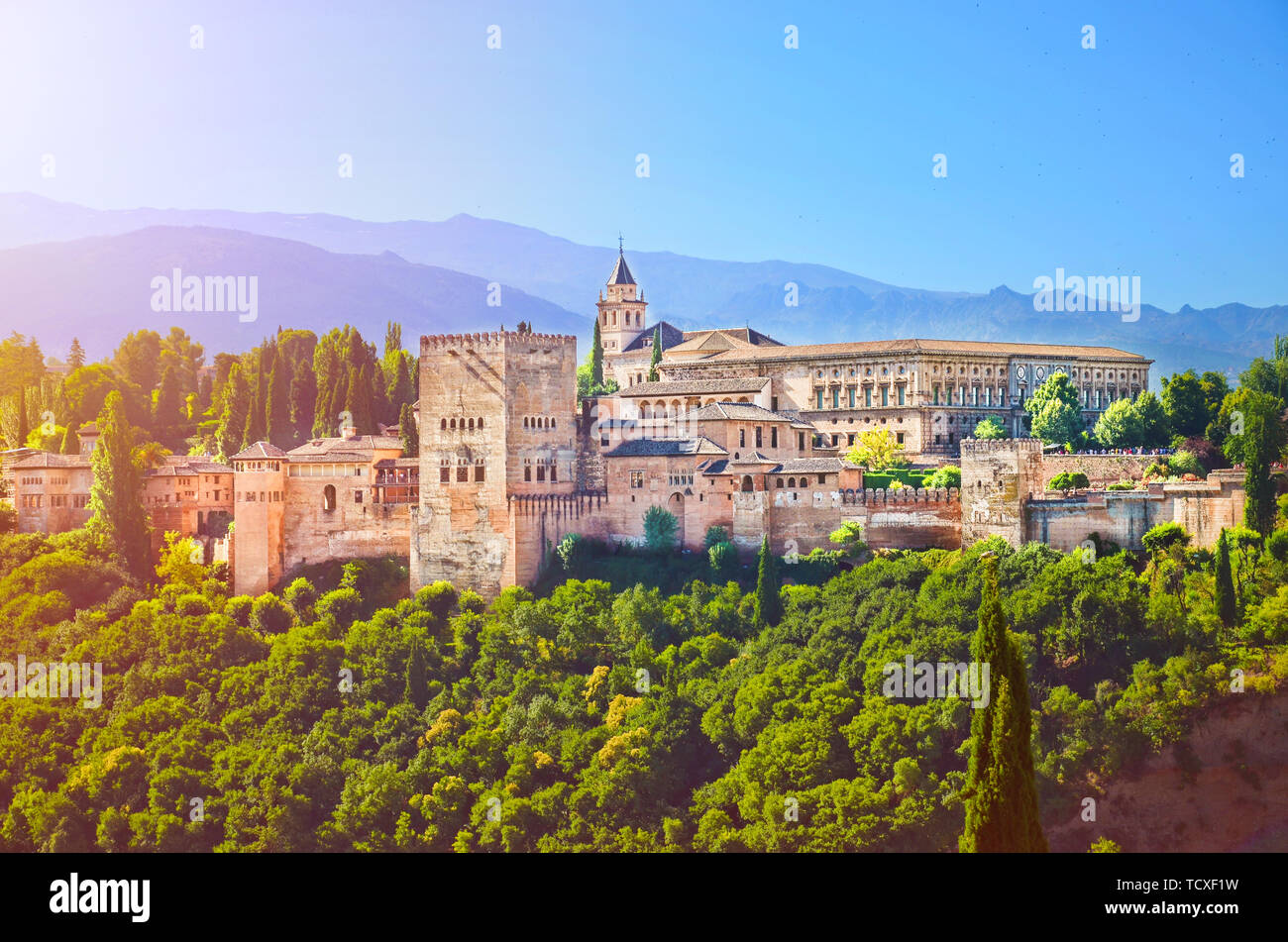 Amazing Alhambra palace complex taken in the morning in sunrise light. Beautiful piece of Moorish architecture, surrounded by green trees, is located in Granada, Spain. Stock Photo