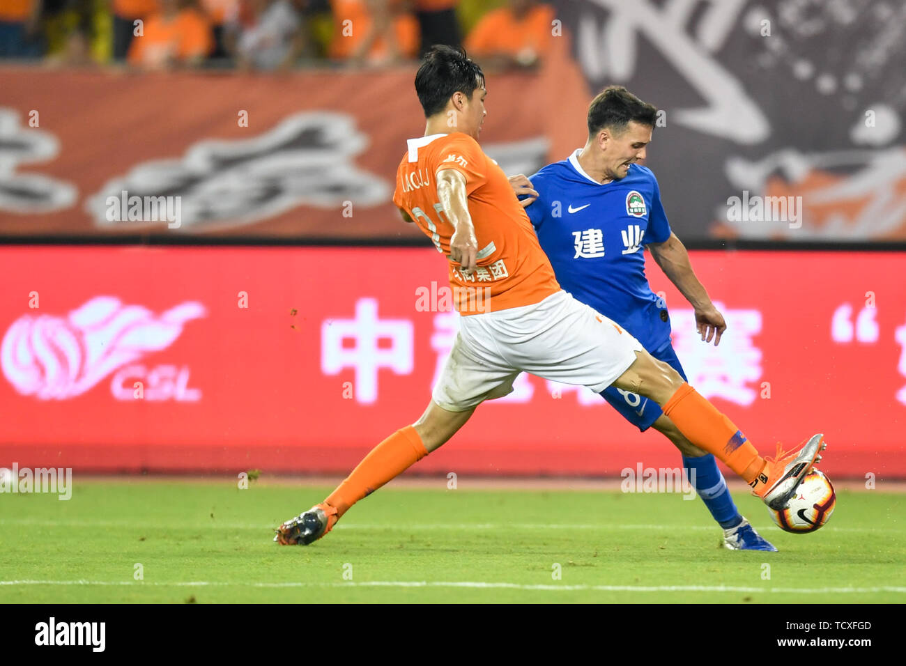 English-born Taiwanese football player Tim Chow, right, of Henan Jianye challenges a player of Wuhan Zall in their 4th round match during the 2019 Chinese Football Association Super League (CSL) in Wuhan city, central China's Hubei province, 8 June 2019.  Wuhan Zall played draw to Henan Jianye 0-0. Stock Photo