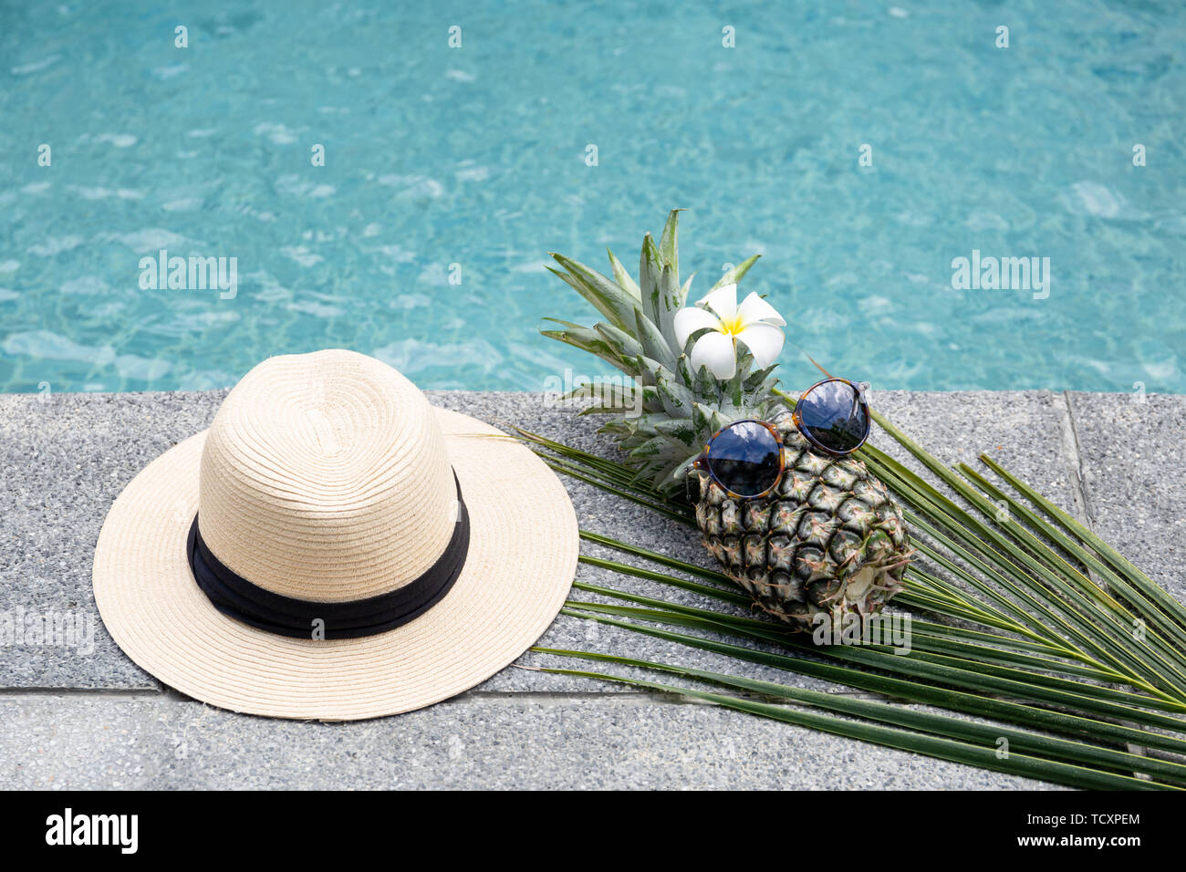 Funny pineapple with sunglasses and flower and hat by swimming pool. Stock Photo