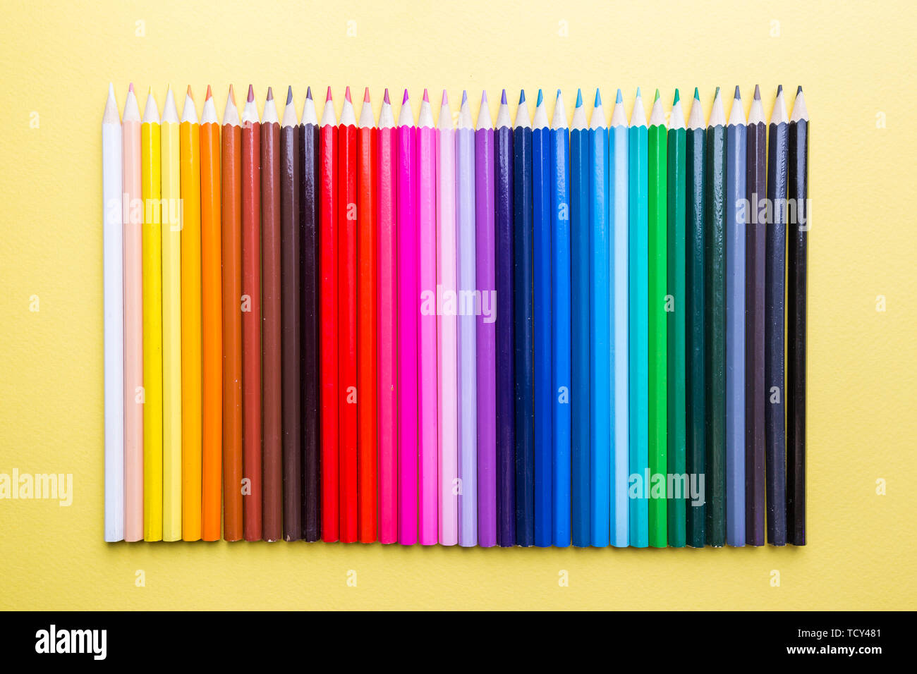 Pencils of various colors on a yellow background, top view with copy space, flat lay - Stock Image