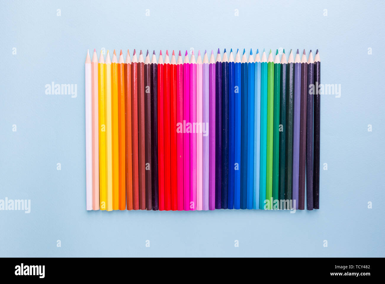Pencils of various colors on a blue background, top view with copy space, flat lay - Stock Image