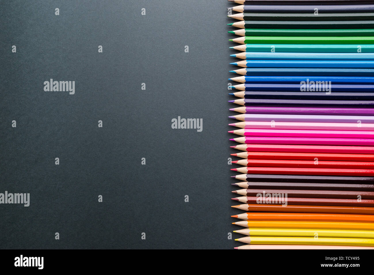 Pencils of various colors on a black background, top view with copy space, flat lay - Stock Image