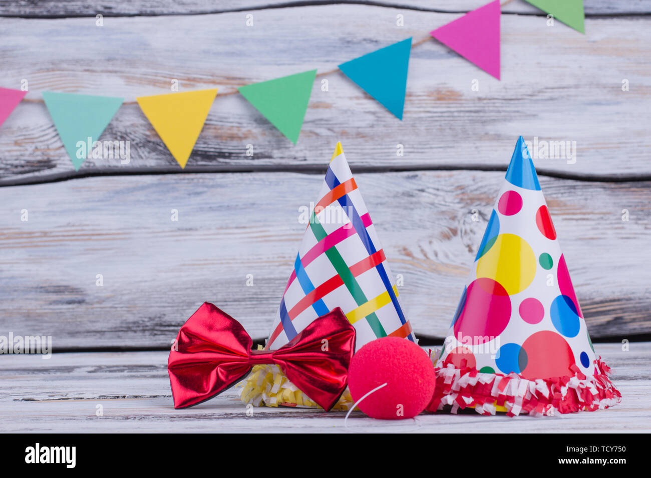 Party hats and other stuff on wooden background. Colorful