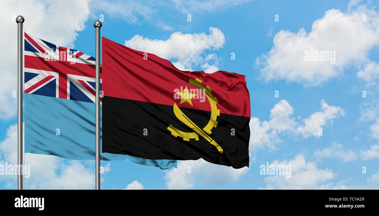 Fiji and Angola flag waving in the wind against white cloudy blue sky together. Diplomacy concept, international relations. - Stock Image