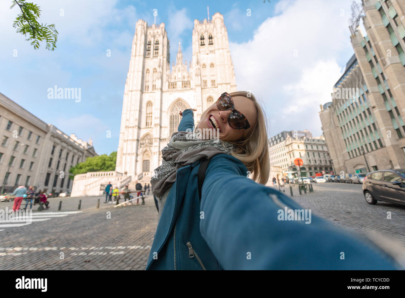 Woman tourist makes a photo about Brussels Cathedral or Saint Michel et Gudula Cathedral in Brussels, Belgium - Stock Image