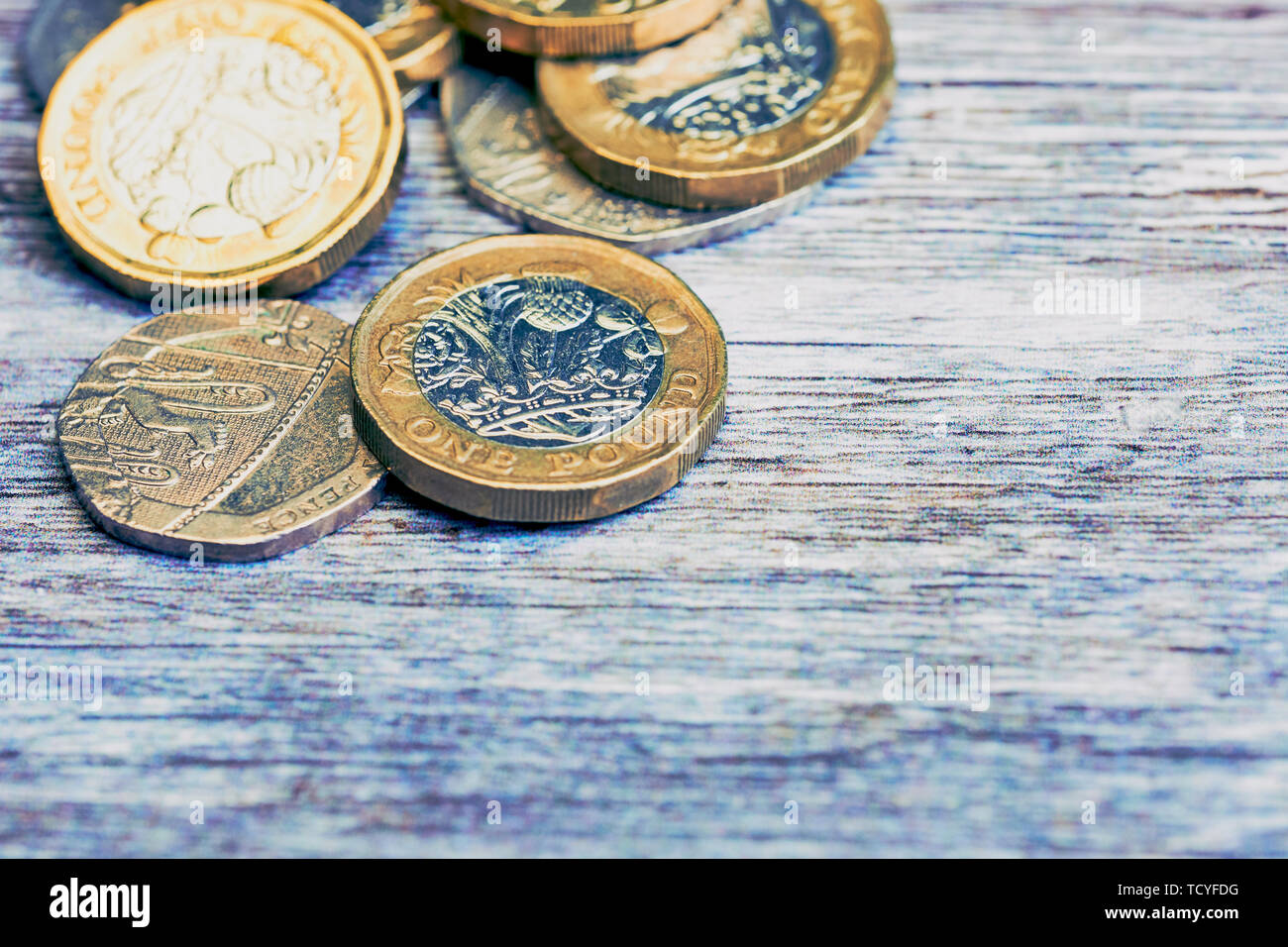macro of British one pound sterling coins in cold color style on wooden surface - Stock Image