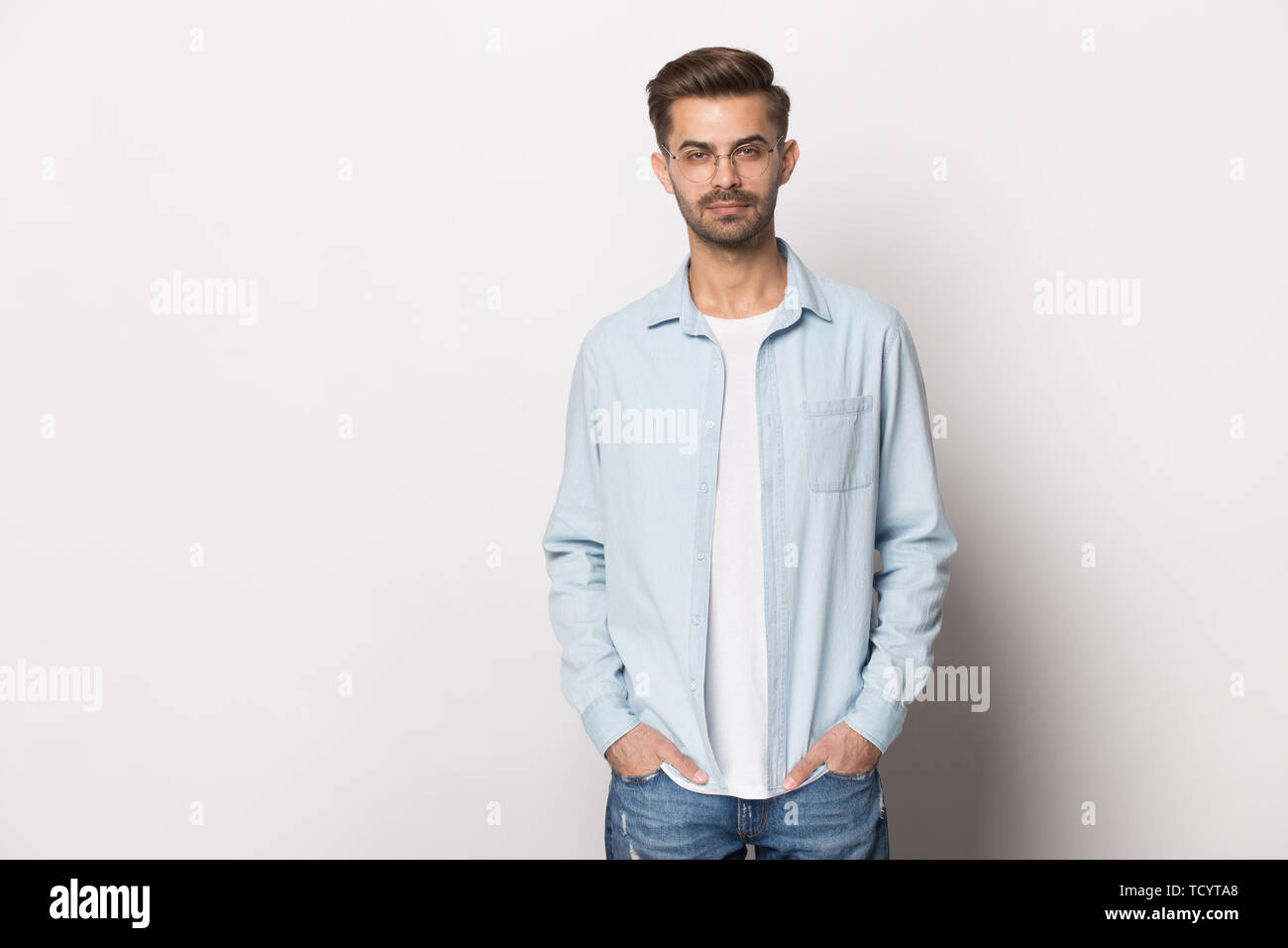 Serious millennial guy wearing glasses casual clothes posing studio shot - Stock Image