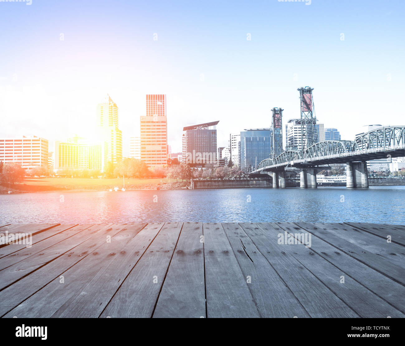 empty wood floor near steel bridge over water with cityscape and skyline of portland at sunrise Stock Photo