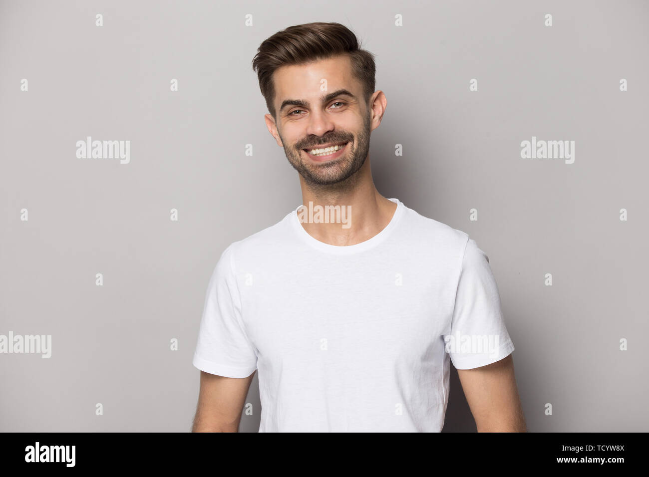 Attractive positive guy with snow-white smile looking at camera - Stock Image