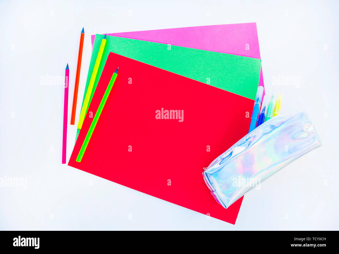 Colorful paper, neon pencils and holographic pencil case on white background with copyspace. Flat lay style. Back to school concept. - Stock Image