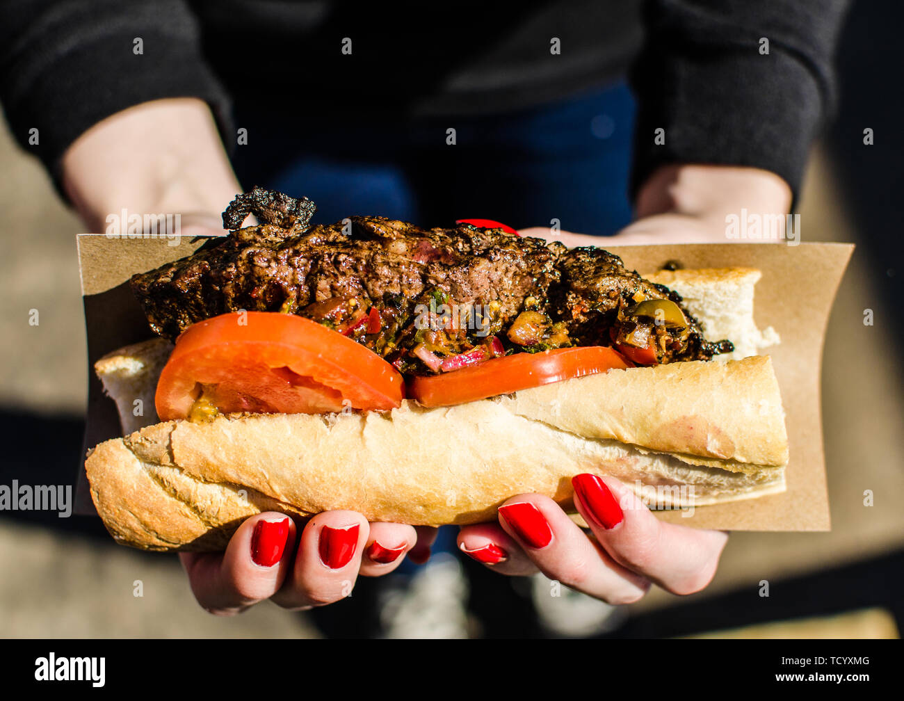 Argentina street food, sandwich with New York strip steak and chimichurri sauce - Stock Image