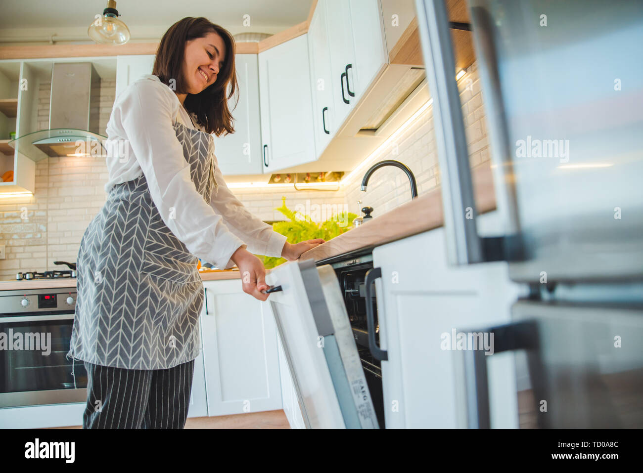 young pretty woman putting dishes in dishwasher Stock Photo